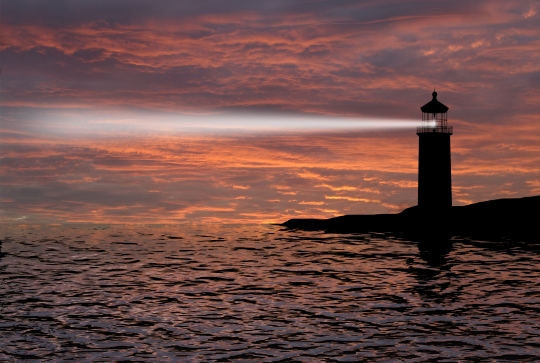 Lighthouse searchlight beam through marine air at night.